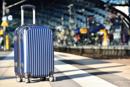 Plastic travel suitcase on the railroad platform Stockfoto