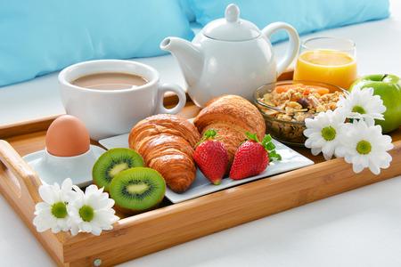 Bandeja de desayuno en la cama en la habitación del hotel.