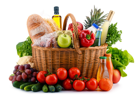 alimentacion balanceada: Wicker basket with assorted gorcery products isolated on white Foto de archivo