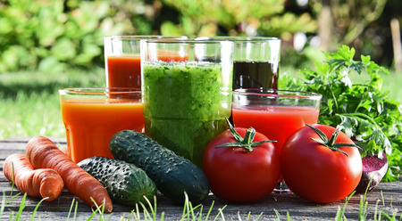 Glasses with fresh organic detox juices in the garden. Stock Photo