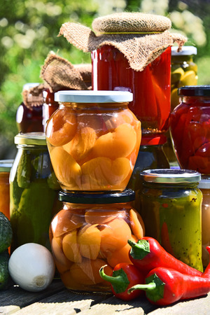 pickling: Jars of pickled vegetables and fruits in the garden. Marinated food. Stock Photo