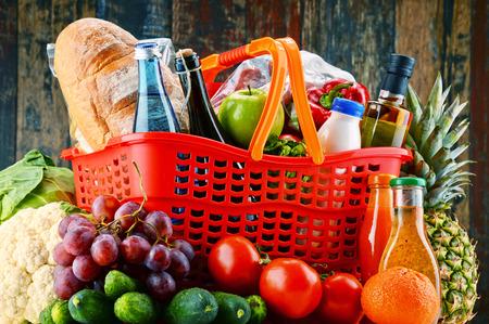 Cesta de compras de plástico con productos de abarrotes surtidos.