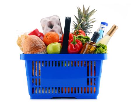 Cesta de compras de plástico con surtido de productos de supermercado aislados en blanco