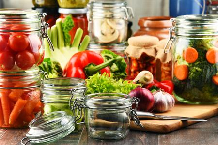 produits alimentaires: Jars avec de la nourriture marinés et légumes crus sur une planche à découper.