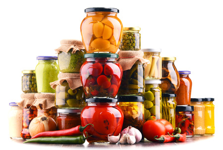 Jars with variety of pickled vegetables isolated on white. Preserved food