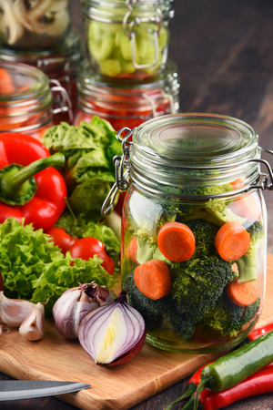 produits alimentaires: Jars with marinated food and raw vegetables on cutting board.