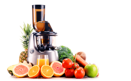 Slow juicer with organic fruits and vegetables isolated on white. Detox diet