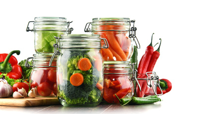 Jars with marinated food and raw vegetables isolated on white. Stock Photo