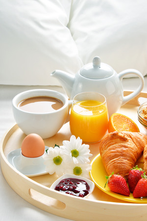 king size bed: Breakfast tray in bed in hotel room. Stock Photo