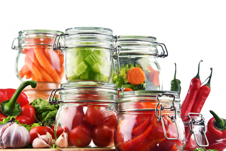 produits alimentaires: Jars with marinated food and raw vegetables isolated on white. Banque d'images
