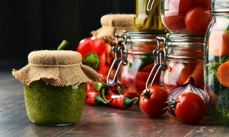 Jars with marinated food and organic raw vegetables. Stock Photo