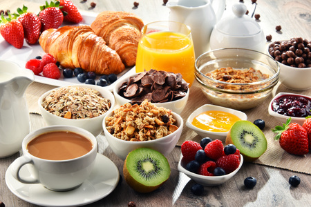 eating utensil: Breakfast served with coffee, orange juice, croissants, cereals and fruits. Balanced diet.