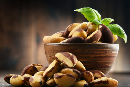 Bowl with Brazil nuts on wooden table. Delicacies