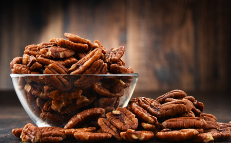 Bowl with pecan nuts on wooden table. Delicacies Stock Photo