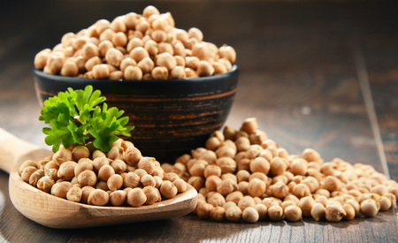 Composition with bowl of chickpeas on wooden table. Stock Photo