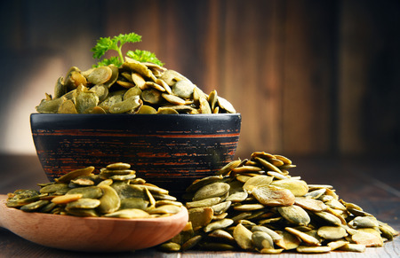 Composition with bowl of pumpkin seeds on wooden table. Stock Photo