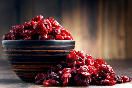 Composition with bowl of dried cranberries on wooden table.
