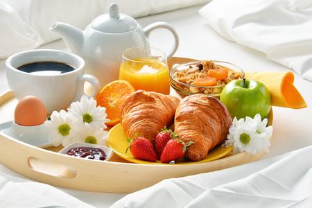 Breakfast tray in bed in hotel room. Stock Photo