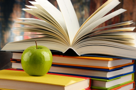 Composition with hardcover books and apple. Stock Photo