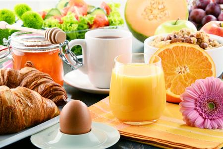 Breakfast consisting of fruits, orange juice, coffee, honey, bread and egg. Balanced diet.