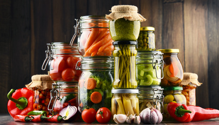 Jars with marinated food and organic raw vegetables. Reklamní fotografie