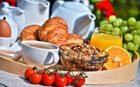 eating utensils: Breakfast served with coffee, orange juice, croissants, cereals and fruits in the garden