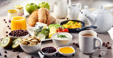 Breakfast served with coffee, orange juice, cheese, cereals and scrambled eggs. Balanced diet. Stock Photo - 83530414
