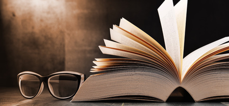 glossary: Composition with open book and glasses on the table. Stock Photo
