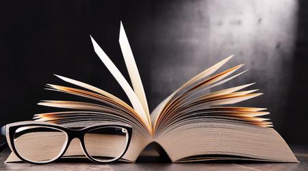 Samenstelling met open boek en een bril op de tafel.