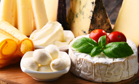 Different sorts of cheese on kitchen table. Stock Photo