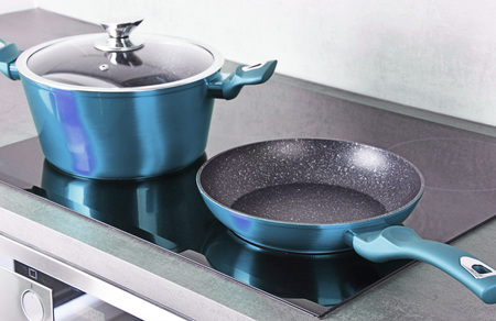 Frying pan and steel pot on modern induction cooktop.