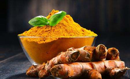 Composition with bowl of turmeric powder on wooden table.