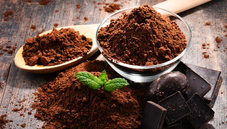 Composition with bowl of cocoa powder on wooden table. Stockfoto