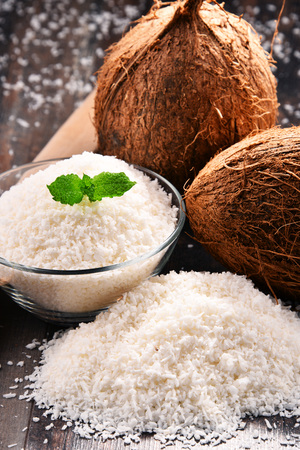 Composition with bowl of shredded coconut and shells on wooden table