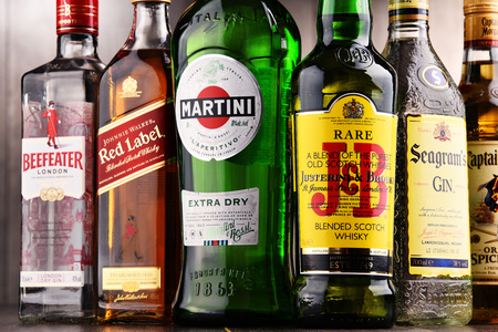 POZNAN, POLAND - DEC 15, 2017: Bottles of assorted global liquor brands including Martini, Johnnie Walker, Captain Morgan, Beefeater, Seagram and JB