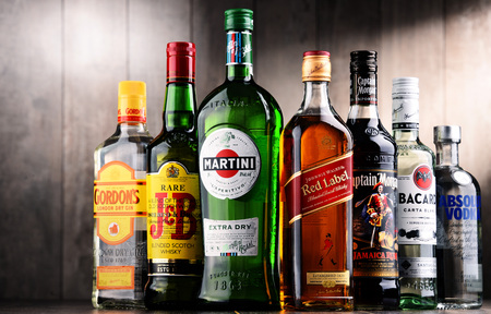 POZNAN, POLAND - DEC 15, 2017: Bottles of assorted global liquor brands including Martini, Johnnie Walker, Captain Morgan, Beefeater, Absolut Vodka, Bacardi, J B and Gordon Imagens - 93039173