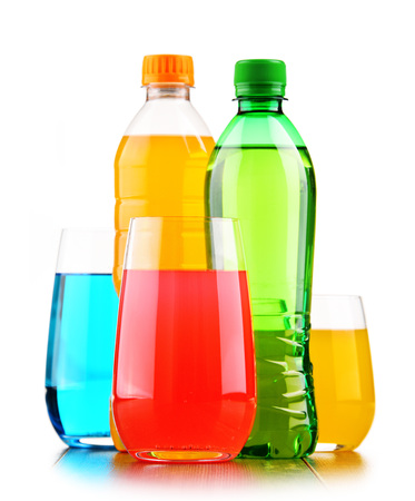 Glasses and bottles of assorted carbonated soft drinks isolated on white