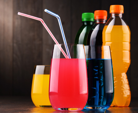 Glasses and bottles of assorted carbonated soft drinks in variety of colors Archivio Fotografico