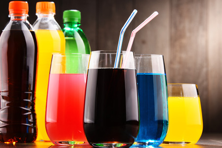 Glasses and bottles of assorted carbonated soft drinks in variety of colors Stok Fotoğraf