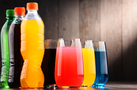 Glasses and bottles of assorted carbonated soft drinks in variety of colors Stockfoto