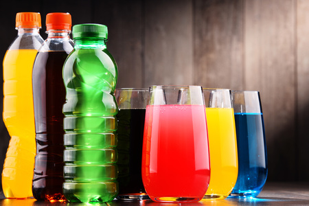 Glasses and bottles of assorted carbonated soft drinks in variety of colors Stock Photo