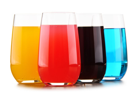 Glasses of assorted carbonated soft drinks isolated on white.