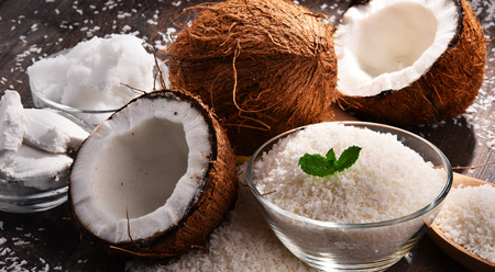 Composition with bowl of shredded coconut and shells on wooden table Stock Photo - 96399408