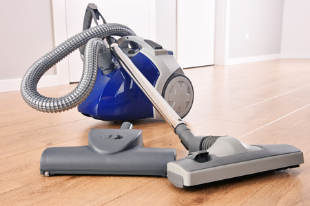 Canister vacuum cleaner for home use on the floor panels in the apartment.