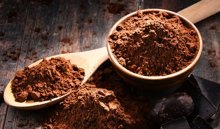 Composition with bowl of cocoa powder on wooden table. Stock Photo