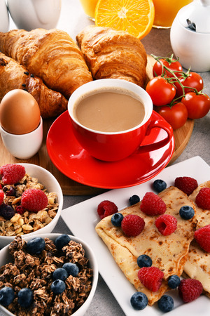 Breakfast served with coffee, orange juice, croissants, egg, cereals and fruits. Balanced diet. Stock Photo - 97376725