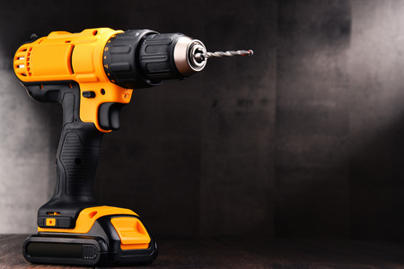 Cordless drill with drill bit working also as screw gun. Stock Photo