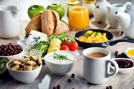 Breakfast served with coffee, orange juice, cheese, cereals and scrambled eggs. Balanced diet. Stock Photo - 101784046