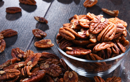 Bowl with pecan nuts on wooden table. Delicacies Stockfoto