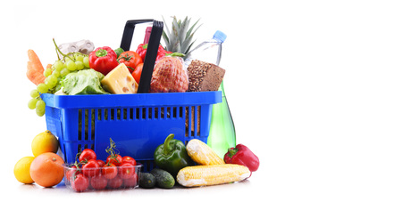 Plastic shopping basket with assorted grocery products isolated on white Banco de Imagens